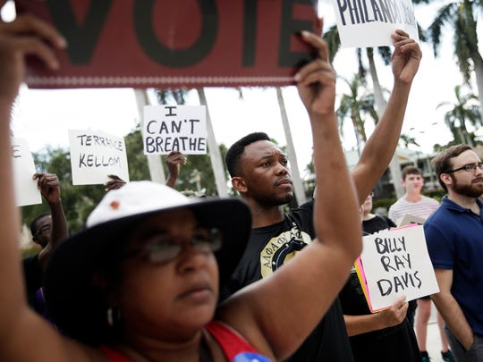 "Nuniez Philor, 24, of Naples, center, holds up a sign that reads ""Philando Castille"" during a Black Lives Matter demonstration in downtown Naples on Sunday, July 31, 2016. The march began at Cambier Park and moved down Fifth Avenue before ending with a protest outside City Hall."