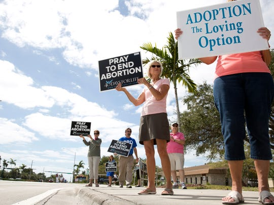 "Phyllis Urban, center, holds a ""pray to end abortion"" sign, with a group of other pro-life advocates, along Goodlette Frank Road just outside the corner of the Planned Parenthood building Tuesday, March 8,  in Naples."