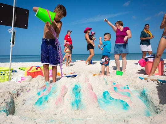 Eight-year-old Maddox Chandler, of Naples, pours a final bucket of colored water onto his sandcastle while participating in the fourth annual Castles for Kids sand sculpting contest with 3-year-old Pito Guerrero, in blue, and Pito's mother, Christi Guerrero, in purple, on Monday, Aug. 1, 2016, at LaPlaya Beach & Golf Resort in North Naples. The event featured a sand sculpting contest, mermaids, pirates, lunch and a raffle and benefitted the Golisano Children's Museum of Naples and