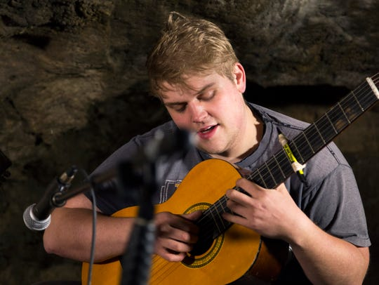 Curt Oren plays guitar inside a cave at Maquoketa Caves