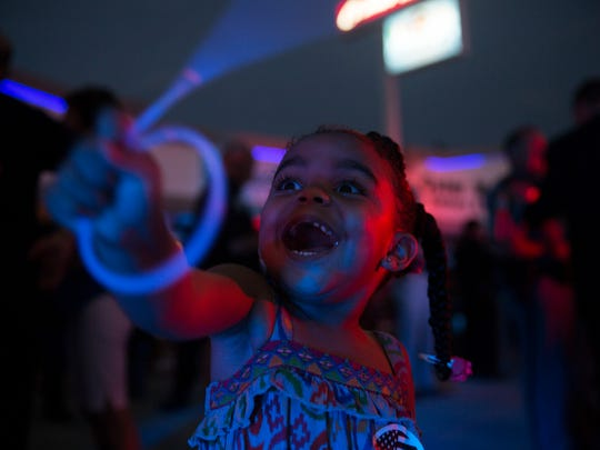 Ava Ashby 3, excitedly waves her blue glow sticks during the pizza fundraiser at Cosmos Cafe & Pizzeria in Naples on August 3, 2016. The fundraiser benefited the Collier County 100 Club, an organization that provides financial assistance to families of Southwest Florida law enforcement officers and first responders who have died in the line of duty.
