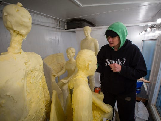 Butter sculptor Sarah Pratt works on a scene from the