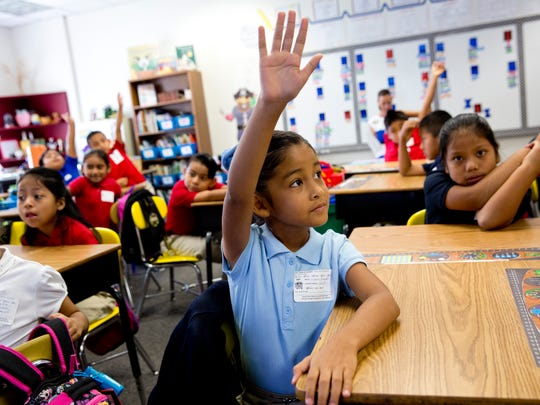 Genesis Fernandez, a second grader at Bonita Springs Elementary, calmly lifts her hand to speak in Mrs. Cessna's class during the first day of school Wednesday, August 10, 2016 in Bonita Springs.
