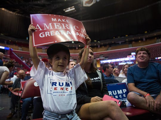 """Ava Setticasi, 5, of West Palm Beach, proudly waves a """"Make America Great Sign"""" during the Donald Trump rally at the BB&T Center in Fort Lauderdale on Aug. 10, 2016."""