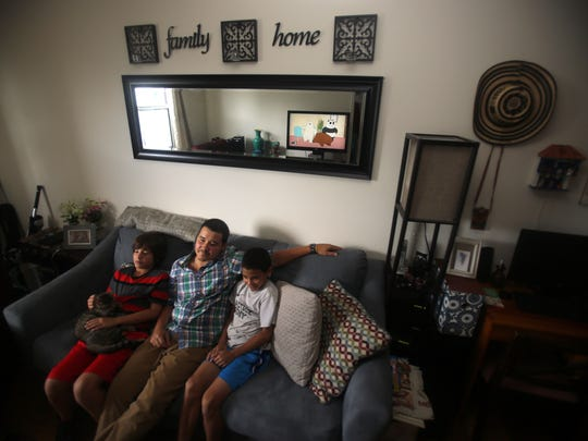 Andres Castro watches television with his twin 10-year old sons, Jarett and Anthony, in their Ossining apartment.