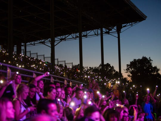 Fans hold their phone flashlights up as Hailee Steinfeld