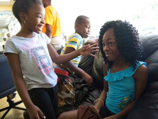 Christelle Prevalus, 8, left, admires Enodia Alincy's, 10, hair at  Excelsior Barbershop Saturday, August 13, 2016 in Naples. Wilner Cenecharles, the owner of the shop, is offering free haircuts for kids as a back to school special at the shop this weekend.
