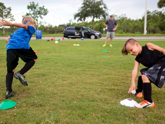 Sloan Morrison, left, 7, and his little brother Zane, 5, practice running drills for their upcoming soccer tryouts as their father, Michael Morrison, watches at North Collier Regional Park Wednesday, August 17, 2016 in Naples. The Collier County Planning Advisory Board is considering North Naples Regional Park as a possible expansion site to grow the counties' sports tourism. Expanding the park could mean reducing the preserves, where there are biking and walking paths.