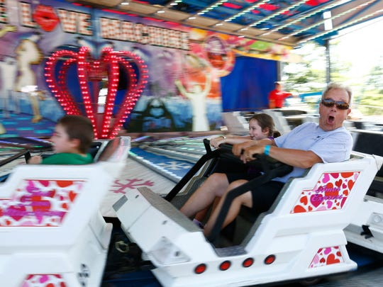 People enjoy riding a Wisconsin Valley Fair's ride Tuesday afternoon at the Marathon Park in Wausau.