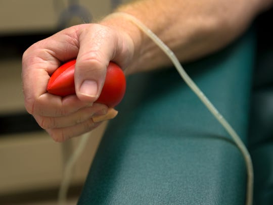 Larry Lasky, of Naples, squeezes a stress ball to aid