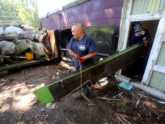 "Workers remove debris from an abandoned home at  14 Suffern Lane in the Town of Haverstraw Aug. 23, 2016. This is one of several ""zombie homes"" that Town Supervisor Howard Phillips says the town is cleaning up over concerns for safety and to preserve the appearance of neighborhoods. Phillips said the owners of this home abandoned it over a year ago when they couldn't afford to pay the taxes on the property."