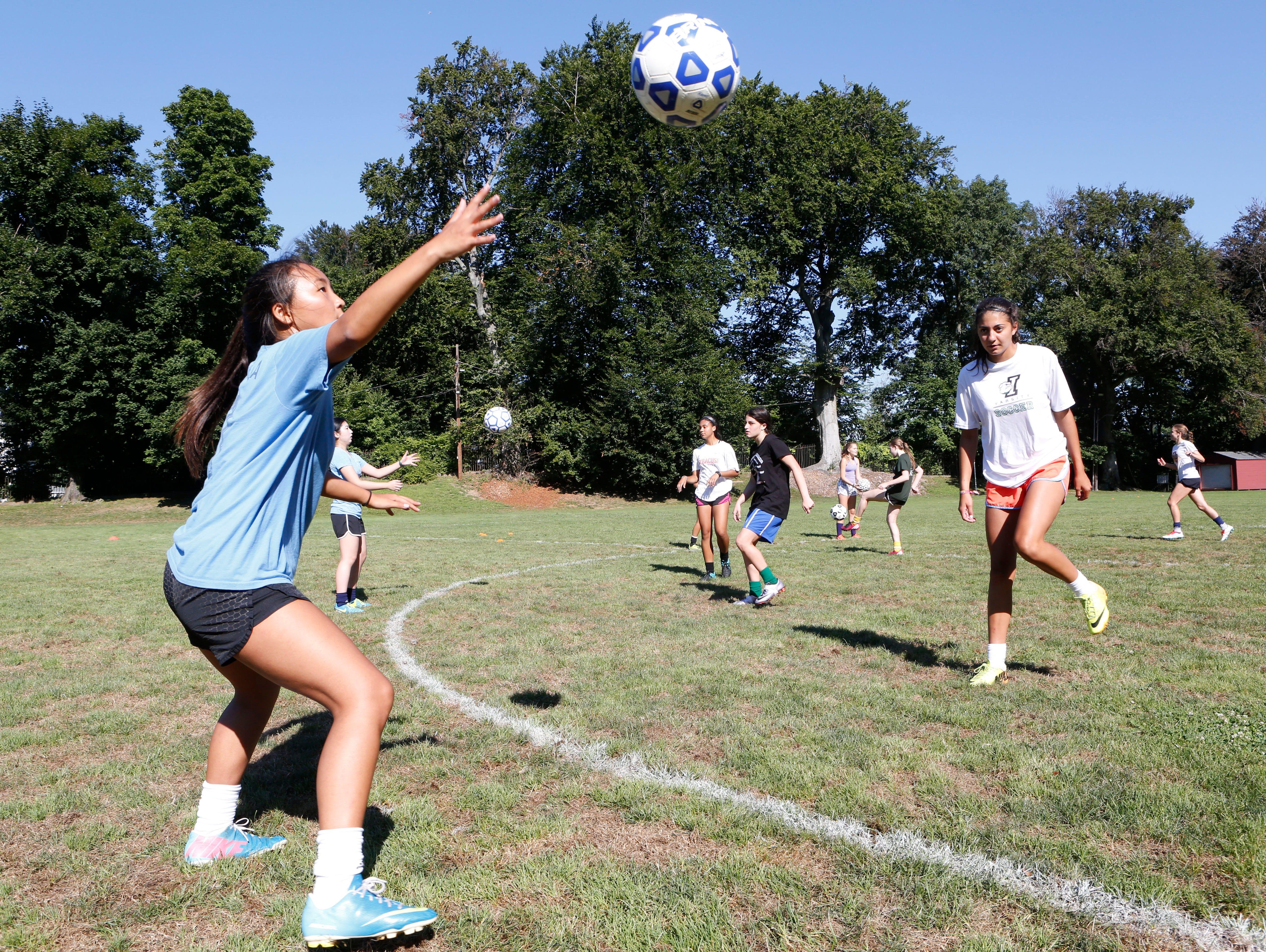 Juniors Okna Freeman, left, and Olivia Valdes run through drills during soccer practice Aug. 24, 2016 at Memorial Field in Irvington.