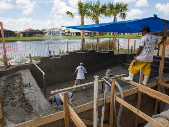 Constructions workers pave an in-ground pool at the