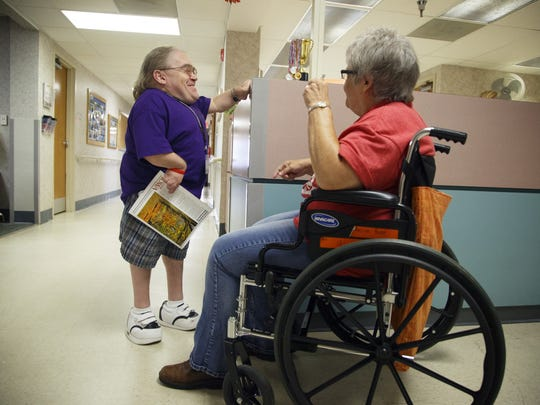 Randy McQueen chats with Marilyn Root, a patient at Mercy Hospital in Oelwein where he volunteers, on Thursday, Sept. 1, 2016. McQueen, who was born with a condition that causes dwarfism, is receiving a national volunteer of year award from the American Healthcare Association.