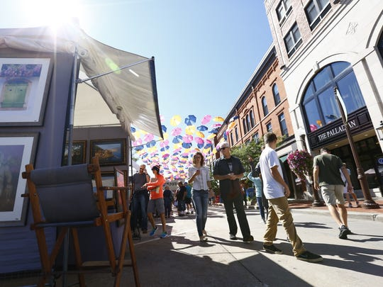 People look through a variety of art displays Sunday during Wausau's Artrageous Weekend in downtown Wausau.