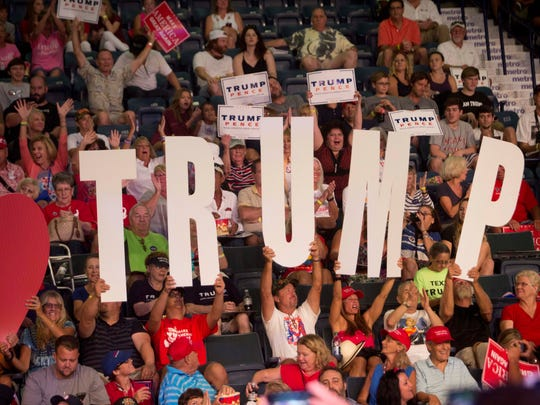 Supporters for Donald Trumo hold up signs before a rally for Donald Trump at Germain Arena.