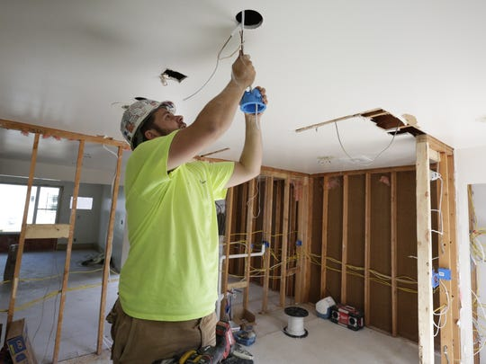 Grant Waters of Kampo Electic works on the electrical wiring inside one of the Cumberland Court apartment buildings.  The Cumberland Court apartments is undergoing a $14 million renovation to the existing buildings along with a new community center.