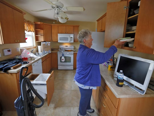 Lynn Stansbery moves items back into her Cedar Rapids home Wednesday, Sept. 28, 2016.