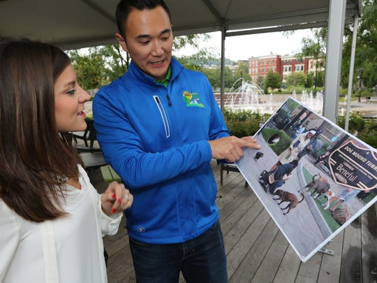 James Sun (right), a Beneful employee, shares plans for upgrades at the Washington Park Dog Park in Over-the-Rhine with Cincinnati resident Sammi Zola at the Beneful Yappy Hour on Thursday.