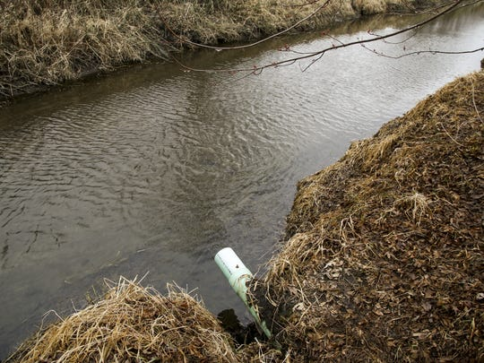 A drainage tile feeds into a stream near an Iowa farmland.