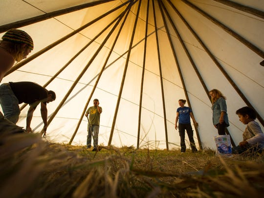 Chet Stoneman, 62, far right, of the Rosebud Indian Reservation in South Dakota guides the assembly of a teepee for a peyote ceremony at the Oceti Sakowin Camp Saturday, Oct. 1, 2016.