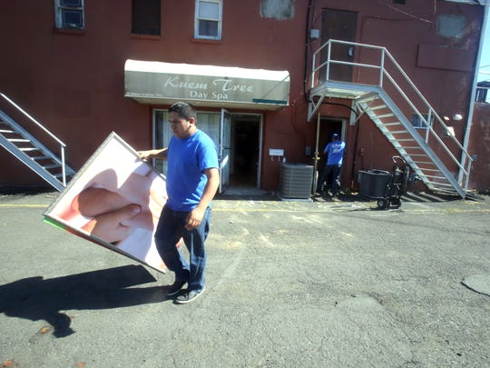 Workers from a moving company remove items Thursday from Keum Tree Day Spa, located behind a strip mall on South Little Tor Road in New City. Rockland County closed down the spa after prostitution arrests there.