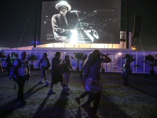 Bob Dylan is seen performing on an outdoor screen on