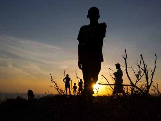 A boy stands on top of the hillside of town of Jeremie, Haiti,  that was destroyed by Hurricane,  Saturday Oct. 8, 2016.  Aid has begun pouring into the hard-hit town,  where thousands of homes were damaged or destroyed and many people were running low on food and facing an increased risk for cholera.  (AP Photo/Dieu Nalio Chery)