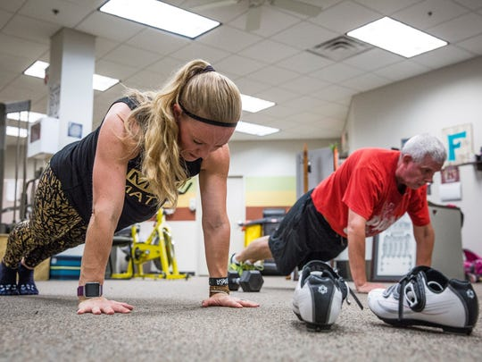 Christy Baker works with Roger Ball on a fitness class during his lunch break Monday afternoon at the Mursix health and wellness room. The organization stresses fitness for their employees by utilizing Baker's skills for advice and fitness classes on weight loss, yoga, weight lifting and more.