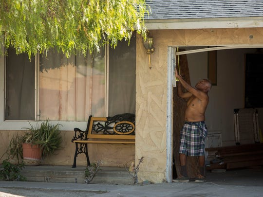 A man believed to be a relative of John Felix works at a home on N. Cypress Road in Palm Springs, the scene of a shooting that killed two police officers.