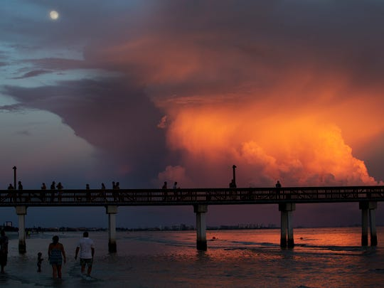 A spectacular sunset reflects off of cumulus clouds as the moon rises on Fort Myers Beach on Tuesday 8/16/2016 evening.