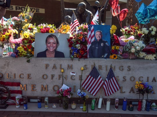 """Flowers are piled onto the memorial in front of the Palm Springs Police Department the day after officers Lesley Zerebny and Jose Gilbert """"Gil"""" Vega were killed."""