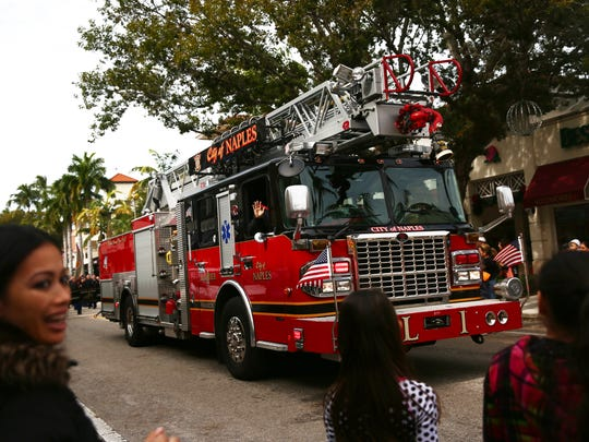 FILE - People wave at a passing fire truck during the 19th annual Martin Luther King, Jr. Day Parade in downtown Naples on Monday, Jan. 18, 2016.