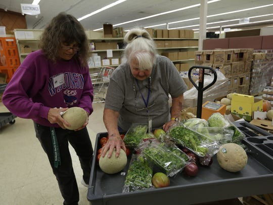 Volunteers Paula Allen and Denise Lien sort fruit and