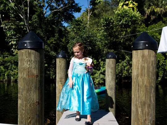 Dressed up as Elsa from the Disney movie Frozen Alexis Camp, 7, watches from the docks as kayakers and paddle boarders make their way down the river as she holds her guinea pig Gidget during the 10th Annual Riverfest at Riverside Park Saturday, October 22, 2016 in Bonita Springs.