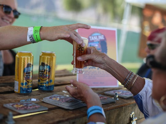 Rotary volunteer Kellie Kennedy hands Wanda Harris, of Indio, a glass of beer at the La Quinta Brewing Co. booth at the Brew in LQ Craft Beer Festival held at the SilverRock Resort in La Quinta on Saturday, October 22, 2016.