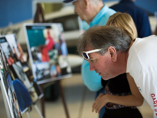 "Chris Campbell, looks over pictures of Congressman Steve Pearce's flight around the world to honor veterans earlier this year. Pearce gave a ""Fly-in"" for local veterans, where he discussed his flight, Saturday October 22, 2016 at the Las Cruces International Airport."