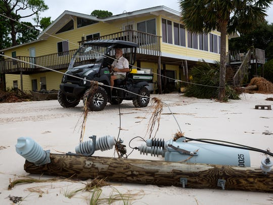 Alligator Point resident Bob Gould uses an all-terrain vehicle to leave his home on Sept. 3, 2016, the day after Hurricane Hermine made landfall nearby. The property is one of several in the community cut off from roads with utilities repeatedly severed by worsening erosion damage.
