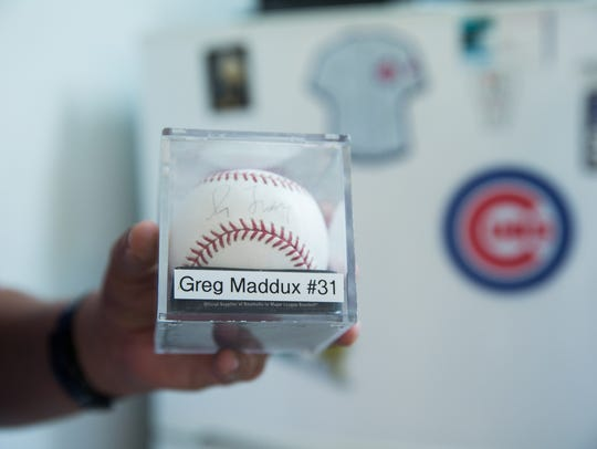 Zach Mirabal, holds up a baseball signed by Greg Maddux.