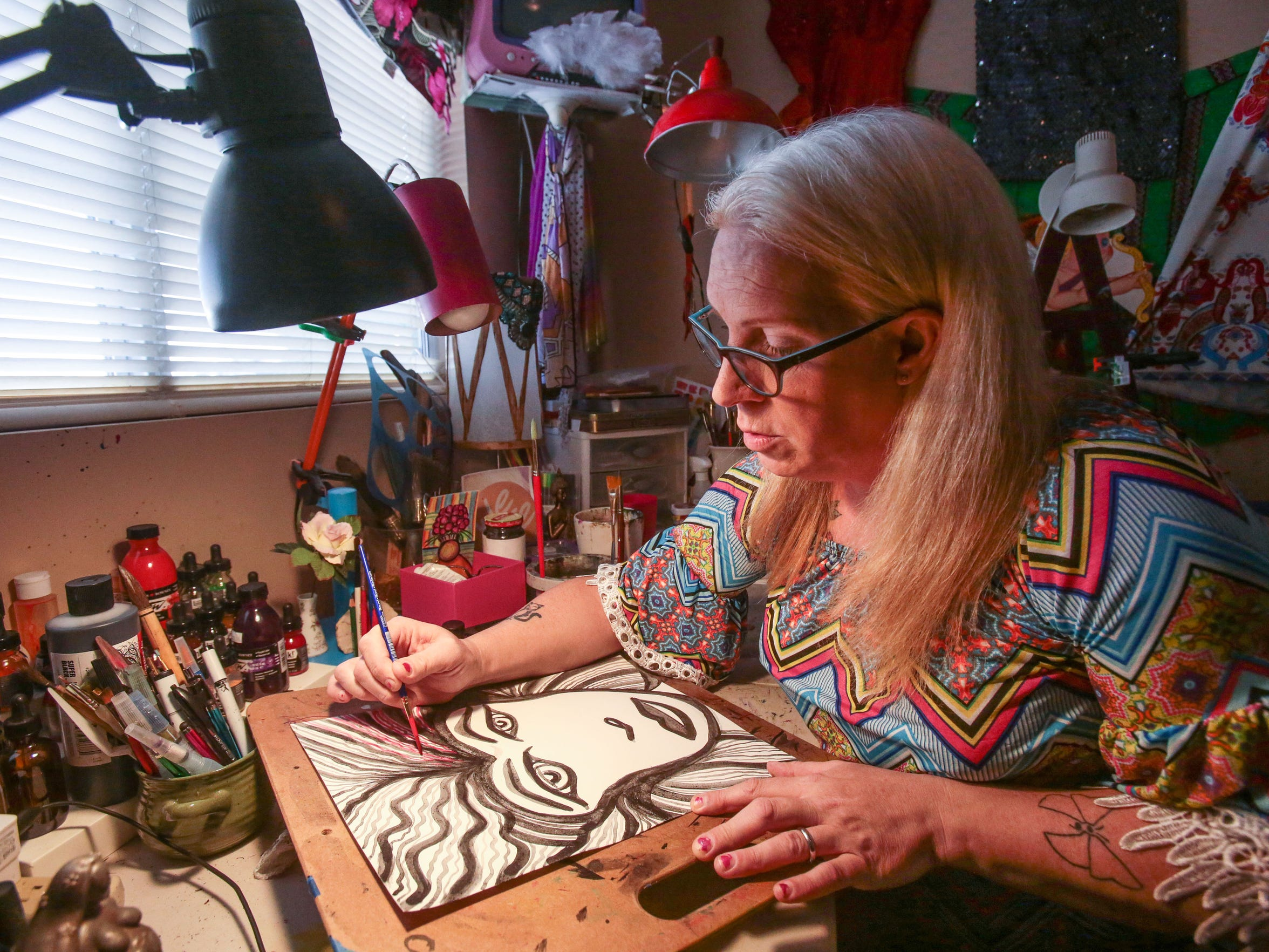 Jennifer Nicole Sweet paints in her home studio in Palm Springs on Tuesday, October 31, 2016. She lives with her wife Candice Marie Sweet who is a sculptor.