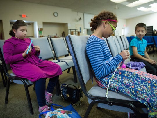 Kerith Grace Baker, left, and her sister Caitlen Baker, crochet, while their brother Kidron looks on, in the sanctuary of First Evangelical Free Church, on Friday, Nov. 4, 2016. The Baker children help their mom crochet hats for kids that are given out through Operation Christmas Child every year.