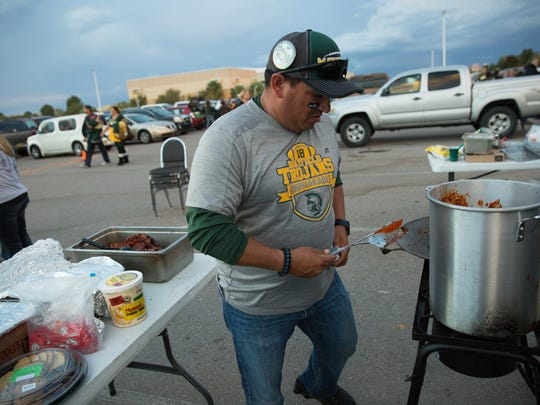 Chris Moreno, part of the Mayfield Tailgate cleans up their tailgate area at Aggie Memorial Stadium parking lot, before heading into the stadium to watch the LCHS, MHS 50th anniversary game, Friday November 4, 2016.