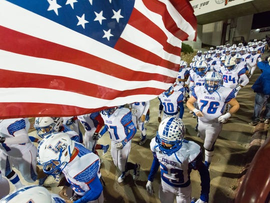 Las Cruces players file onto the field for Friday's District 3-6A game against Mayfield at Aggie Memorial Stadium.