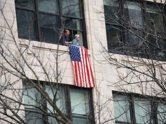Thousands attended and participated in the Veterans Day Parade in Springfield, MO on Sat. Nov. 5, 2016. A couple flies a flag from  the Heers Building.