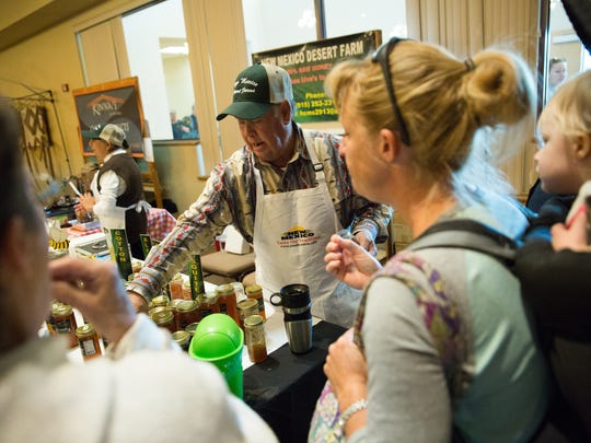Harold Shumate, with New Mexico Desert Farm, a Honey producer, gets samples of different types of honey ranging from Cotton honey to Mesquite Honey to Heather Ratzlaff-Tucker ,right, and he mother Maxine Ratzlaff, left. During the Home Grown show at the New Mexico Farm and Ranch Heritage Museum, Saturday November 19, 2016.