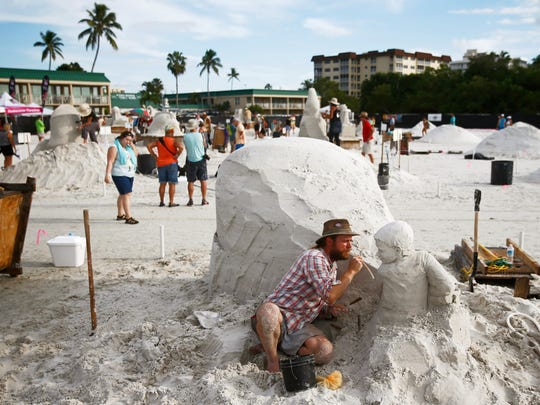 Abe Waterman of Prince Edward Island, Canada, uses a straw to blow off excess sand Friday, Nov. 20, 2015 at Wyndham Garden Hotel Fort Myers Beach.