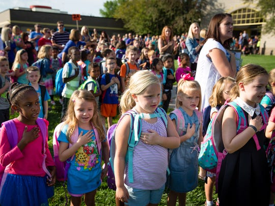 Students gather and say the Pledge of Allegiance before processing into the school on Wednesday, Aug. 24, 2016, on the first day of school at Westridge Elementary School in West Des Moines.