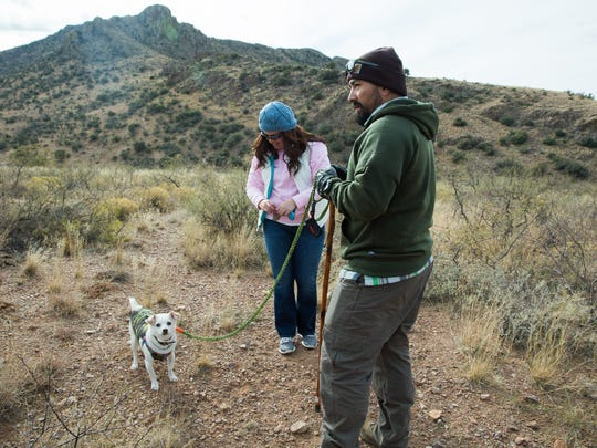 Chris and Marisol Diaz, with their dog Tako, take a break from hiking through Soledad Canyon, during the Opt Outside Hike organized by Friends of Organ Mountains-Desert Peaks, Latino Outdoors and New Mexico Wildlife Federation on Friday, Nov. 25, 2016.