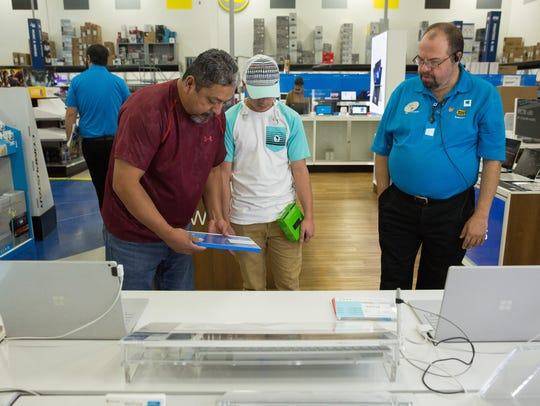 Valente Alvarado and his son Aaron look at the Microsoft