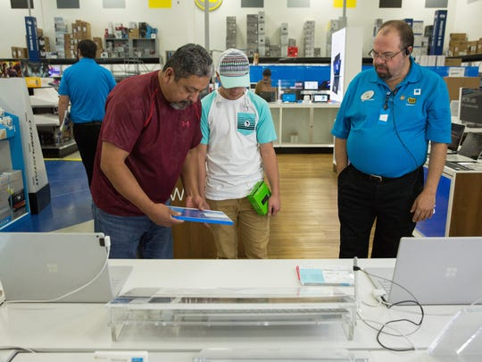 Valente Alvarado and his son Aaron look at the Microsoft Surface Pro 4, while Mark Galt stands ready to answer questions on Friday, Nov. 25, 2016, during Best Buy's Black Friday sale.